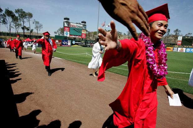 A+graduate+gets+a+high+five+from+a+friend+in+the+stands+during+the+processional+of+the+Elsinore+High+School+graduation+ceremony+at+The+Diamond+in+Lake+Elsinore%2C+CA.+Wednesday%2C+June+1%2C+2016.