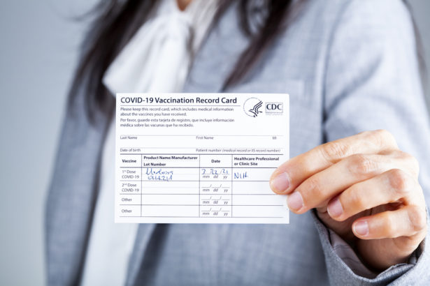 Clarksburg, MD, USA 03-29-2021: A caucasian businesswoman is showing her CDC issued COVID vaccination record card as a proof of immunization. It has the date and lot number on it.